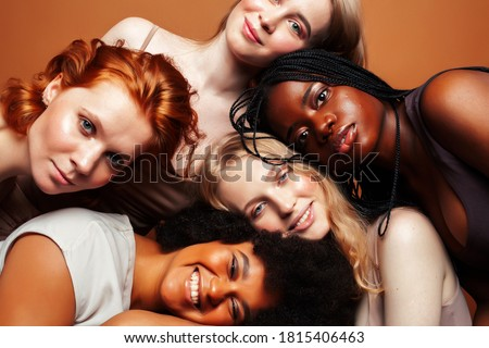young pretty african and caucasian women posing cheerful together on brown background, lifestyle diverse nationality people concept Photo stock ©