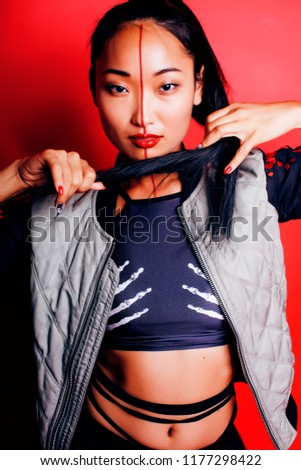 Stock Photo young pretty asian girl posing cheerful on red background, fashi