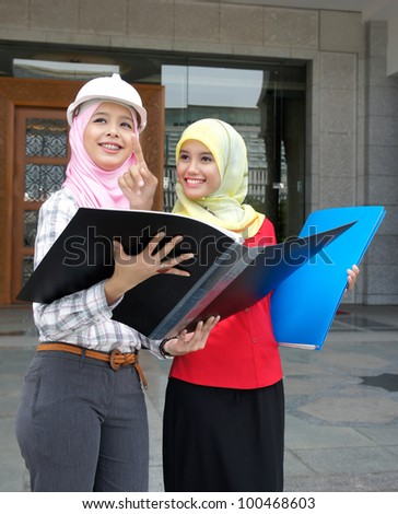 Young pretty Asian muslim college girls having discussion