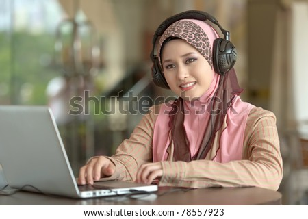 Young pretty Asian muslim woman in head scarf listens to audio with head phone while working on laptop in cafe