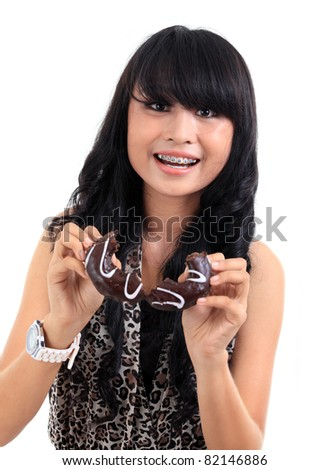 young pretty asian woman eating chocolate donuts