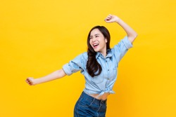 Young pretty Asian woman smiling with energetic movement studio shot isolated on colorful yellow background