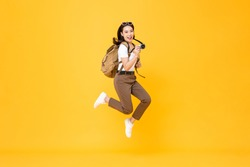 Young pretty Asian woman tourist backpacker smiling and jumping with camera in hand isolated on yellow background