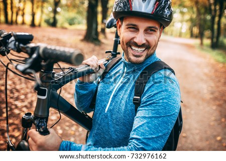 Young pretty athletic man standing with bicycle in autumn park.