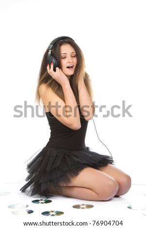 Young pretty attractive female girl  enjoys listening to music in headphones, headset, sitting on the floor with cd disk and sing, wearing fashion evening dress, isolated on white background. - stock photo