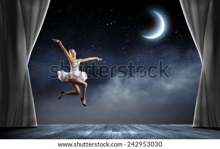 Young pretty ballerina girl making jump in dance