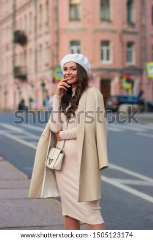 Young pretty beautiful stylish woman in pink dress, white beret hat and beige coat with white leather handbag standing and posing at city street. Fashionable stylish autumn look in pastel colors