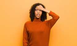 young pretty black woman panicking over a forgotten deadline, feeling stressed, having to cover up a mess or mistake against orange wall