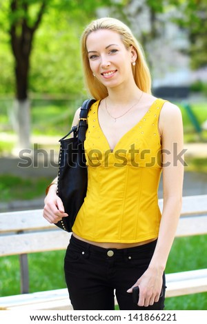 Young pretty blond girl on the walk in the park