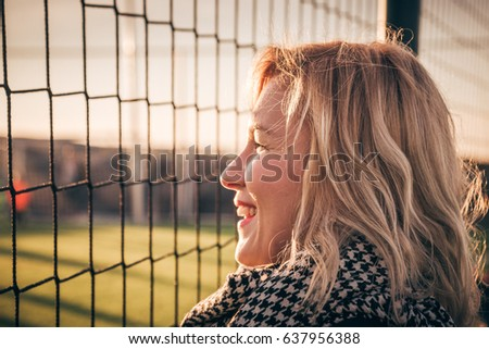 Young pretty blond hair smiling woman - football fan portrait. Aunt cheers for her nephew playing soccer on local green field. Parents picking up kids from their after school activities - concept