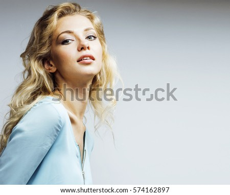 young pretty blond woman smiling on white background close up ma