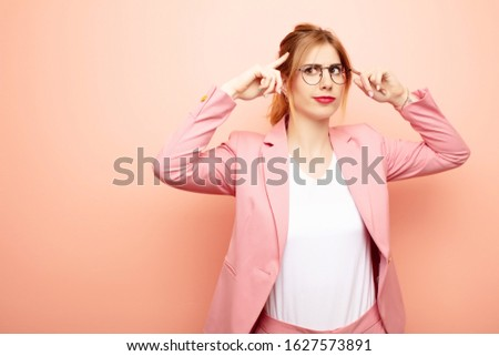 young pretty blonde woman feeling confused or doubting, concentrating on an idea, thinking hard, looking to copy space on side. business concept