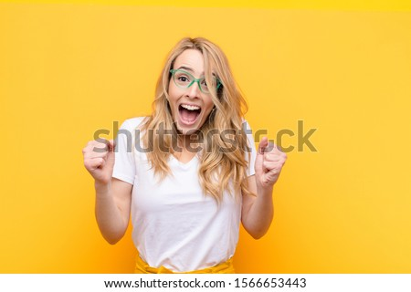 young pretty blonde woman feeling shocked, excited and happy, laughing and celebrating success, saying wow! against flat color wall