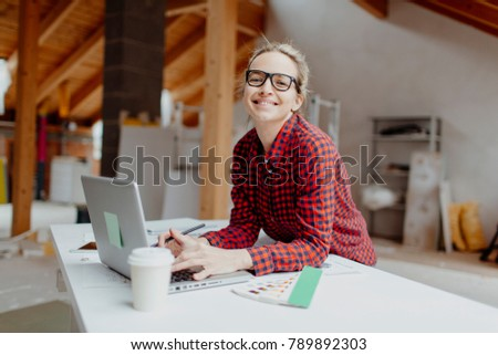 young, pretty, blonde woman is planning on the notebook and tablet the expansion of her loft #789892303