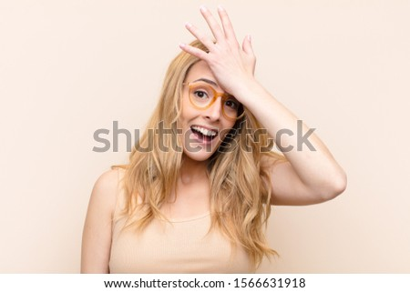 young pretty blonde woman raising palm to forehead thinking oops, after making a stupid mistake or remembering, feeling dumb against flat color wall