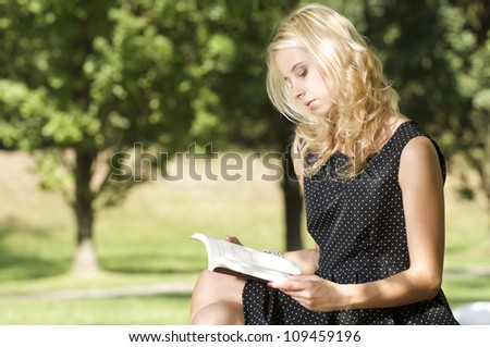 Young pretty blonde woman reading book in park outdoor