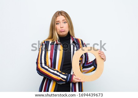 young pretty blonde woman sad, depressed, unhappy, holding the letter O of the alphabet to form a word or a sentence. Foto stock ©