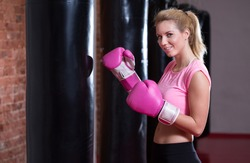 Young pretty boxing girl with pink gloves