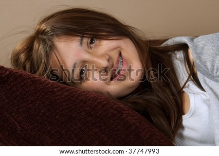 Young pretty brunette hispanic teenage girl with messy hair smiling laying on pillow with braces