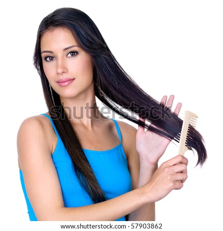 Young pretty brunette woman combing her beautiful long hair - isolated on white background