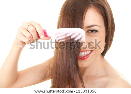 young pretty brunette woman combing her beautiful long hair, white background