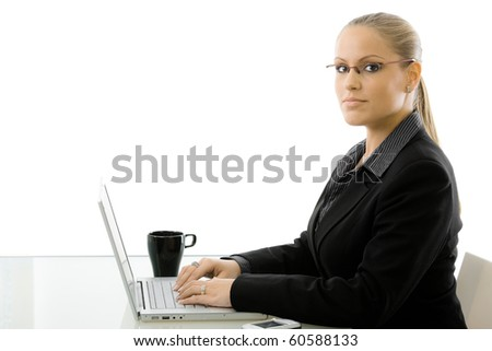 Young pretty businesswoman sitting at desk working on laptop computer, isolated on white background.