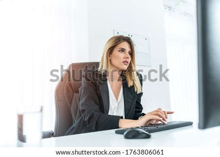 Young pretty businesswoman sitting in her bright office while typing on the keyboard.