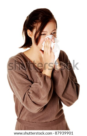 Young pretty caucasian girl blowing her nose.