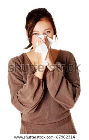 Young pretty caucasian girl blowing her nose. Isolated on white.