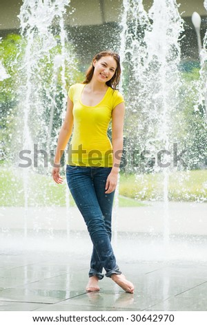 young pretty caucasian lady having fun at an outdoor water fountain