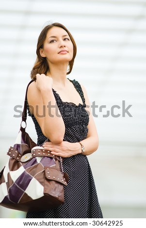 young pretty caucasian lady outdoor with handbag waiting for a friend