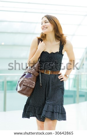 young pretty caucasian lady walking outdoor with handbag