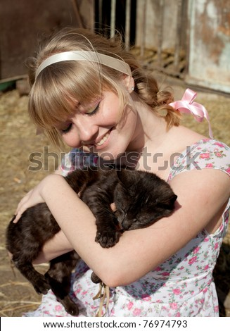 Young pretty cheerful blond woman with cat on a farm