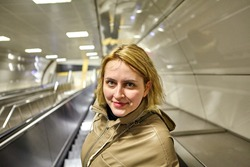 Young pretty cheerful caucasian woman in casual raincoat with blond hair is standing on the escalator in the subway of Istanbul.