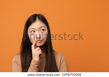 Young pretty chinese woman looking sideways with doubtful and skeptical expression.