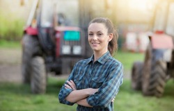 Young pretty farmer woman standing on farmland with crossed arms and tractors in background