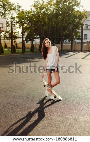 Young pretty fashion brunette girl posing on sport backyard of school in summer holiday with skateboard in hands. swag hipster style