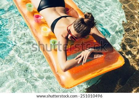 Young pretty fashion woman body posing in summer in pool with clear water lying on mattress in black bikini and having fun