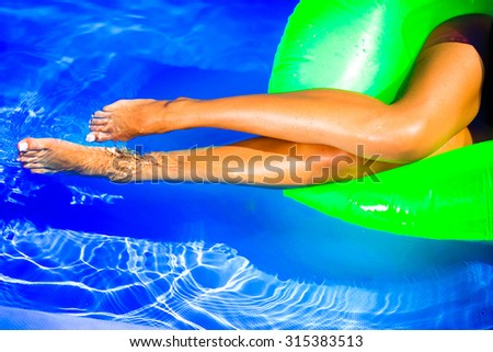 Young pretty fashion woman body posing in summer in pool with clear water lying on mattress in black bikini and having fun.long legs,relaxing time,chilling time,holidays,pool party,wet body,laying