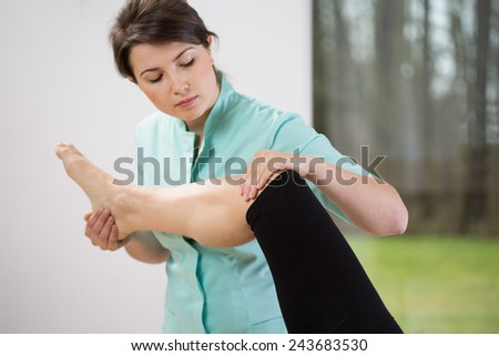 Young pretty female physiotherapist flexing patient\'s knee