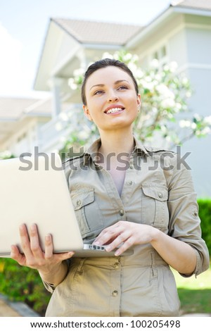 Young pretty female realty agent with laptop presenting beautiful detached house
