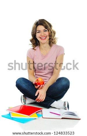Young pretty female student with red apple isolated on white background