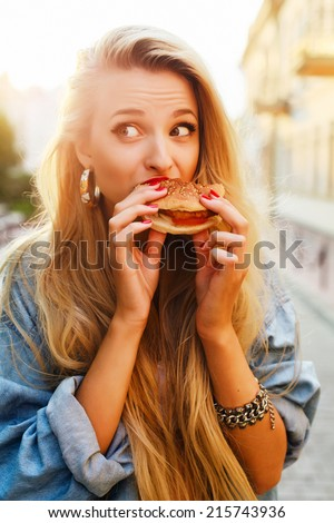 Young pretty funny fashion sensual blond girl eats hamburger fast food sandwich on the street lifestyle outdoor photo