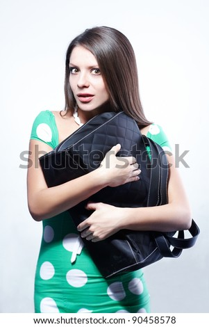 Young pretty girl embracing her bag with scared expression