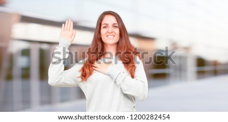 young pretty girl full body smiling confidently while making a sincere promise or oath, solemnly swearing with one hand over heart.
