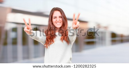 young pretty girl full body with a proud, happy and confident expression; smiling and showing off success while gesturing victory with both hands, giving an