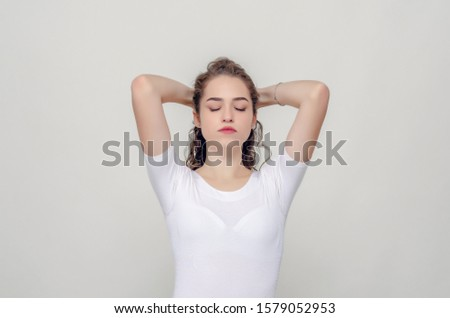 Young pretty girl gathered hair from behind, elbows forward, hands behind head.