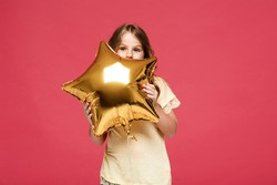 Young pretty girl holding baloon over pink background.