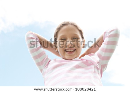 Young pretty girl holding her hair back against a blue sky background.