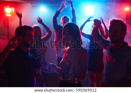 Young pretty girl in shining top dancing with male friends at student disco party and enjoying music with her eyes closed